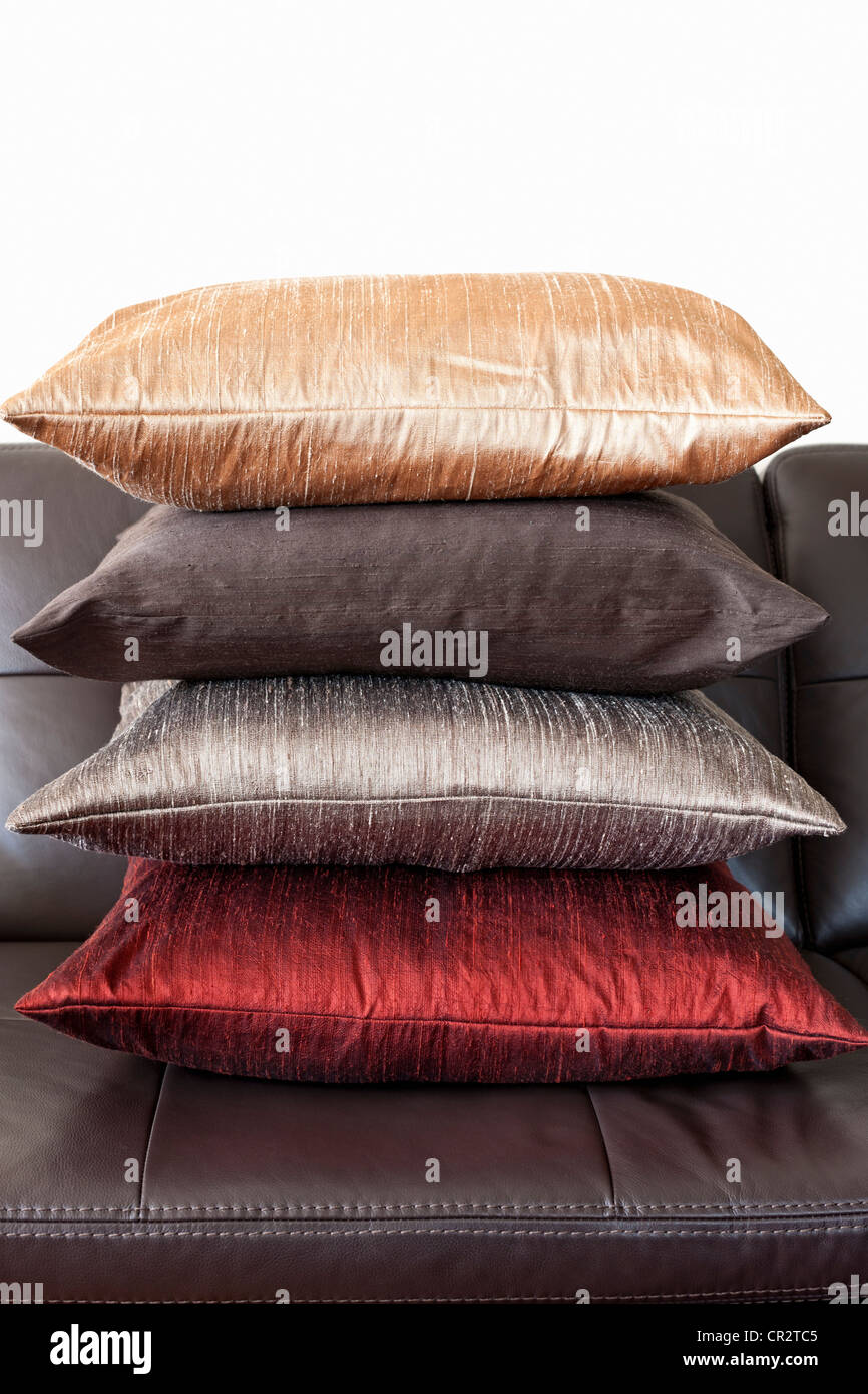 Four colorful cushions stacked on dark brown leather couch Stock