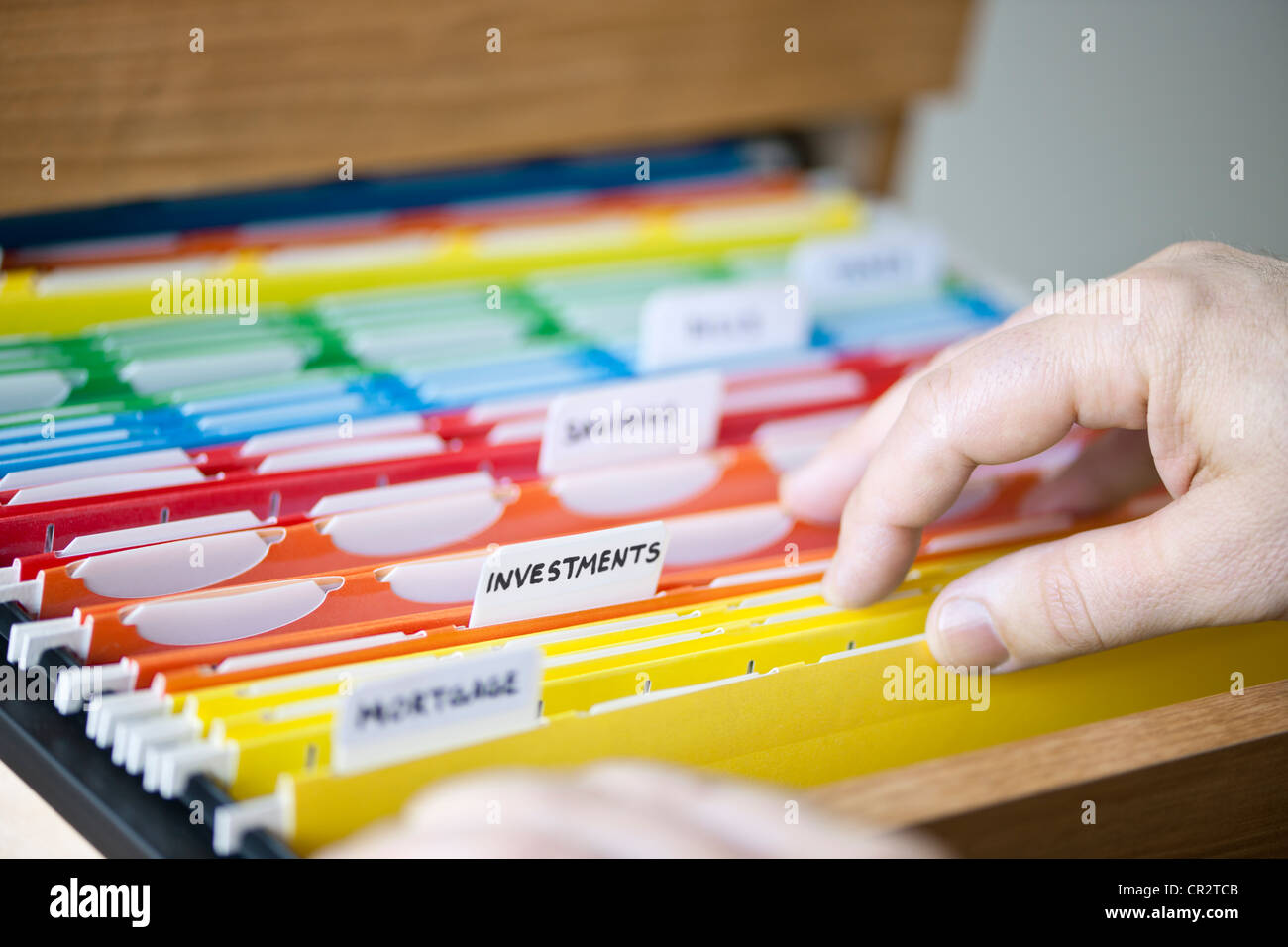 Hands searching through file folders with personal finance documents - Stock Image