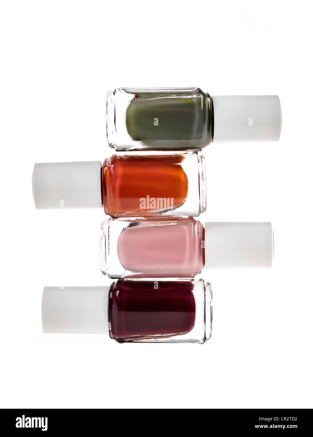 Nail polish bottles of various colors stacked isolated on white ...