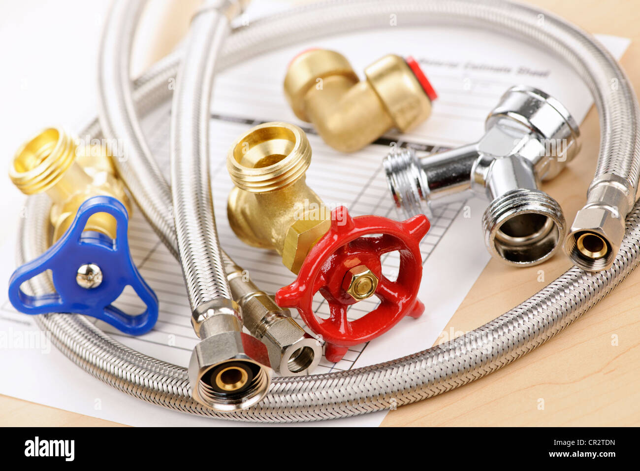 Plumbing valves hoses and assorted parts with estimate sheet - Stock Image