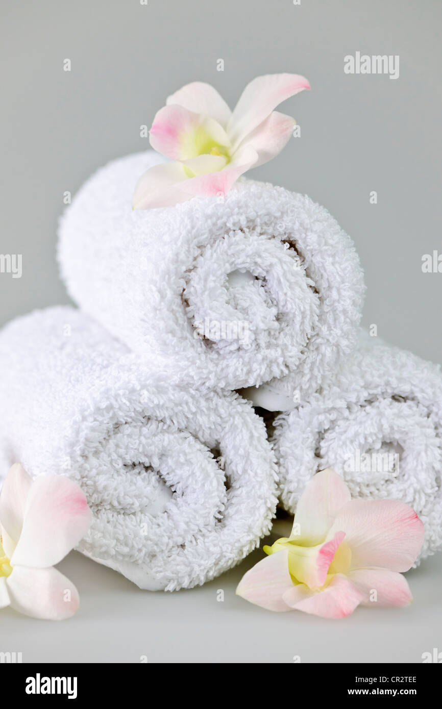 White rolled up spa towels with orchids flowers - Stock Image