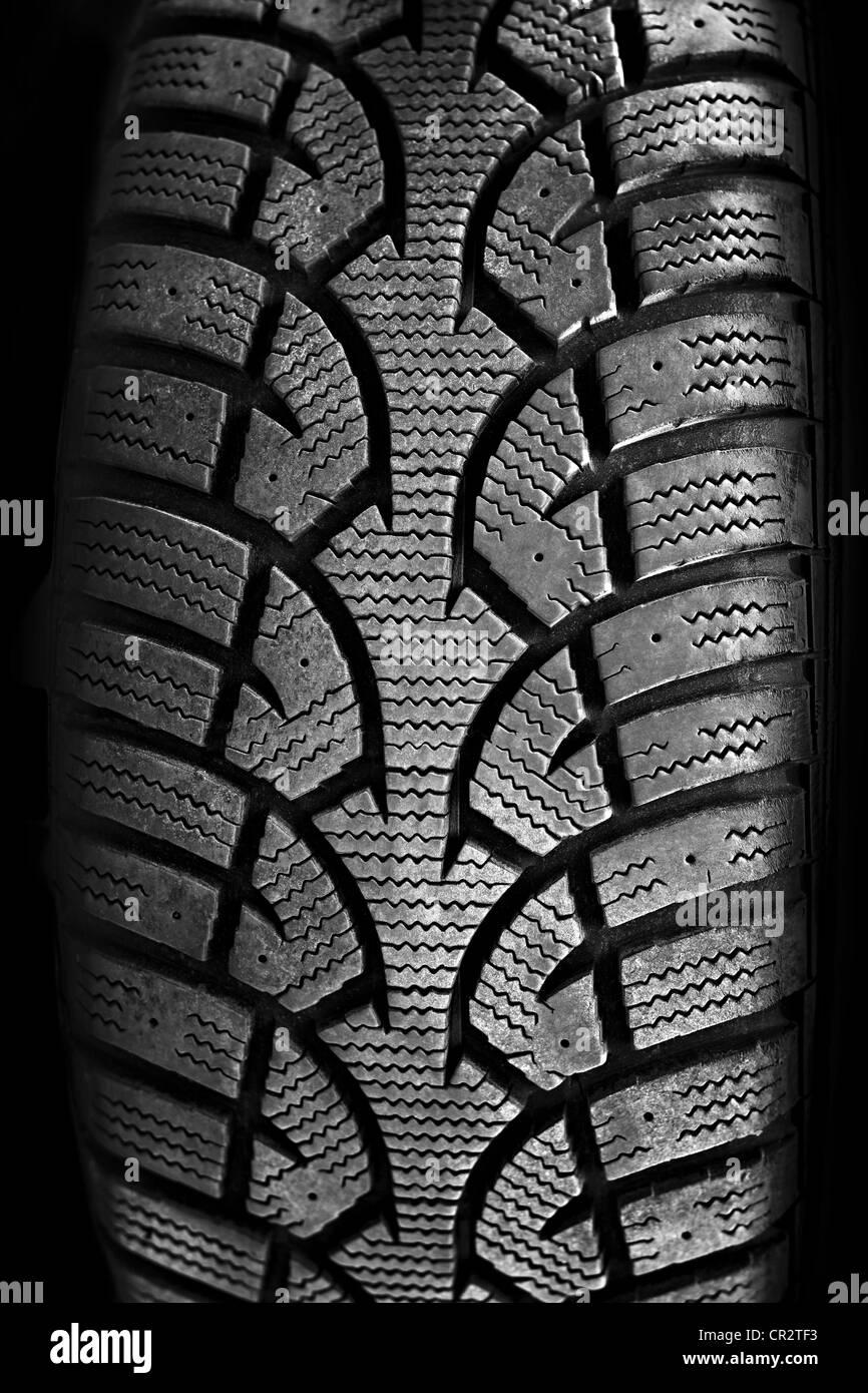 Closeup on rubber tire tread of car wheel - Stock Image