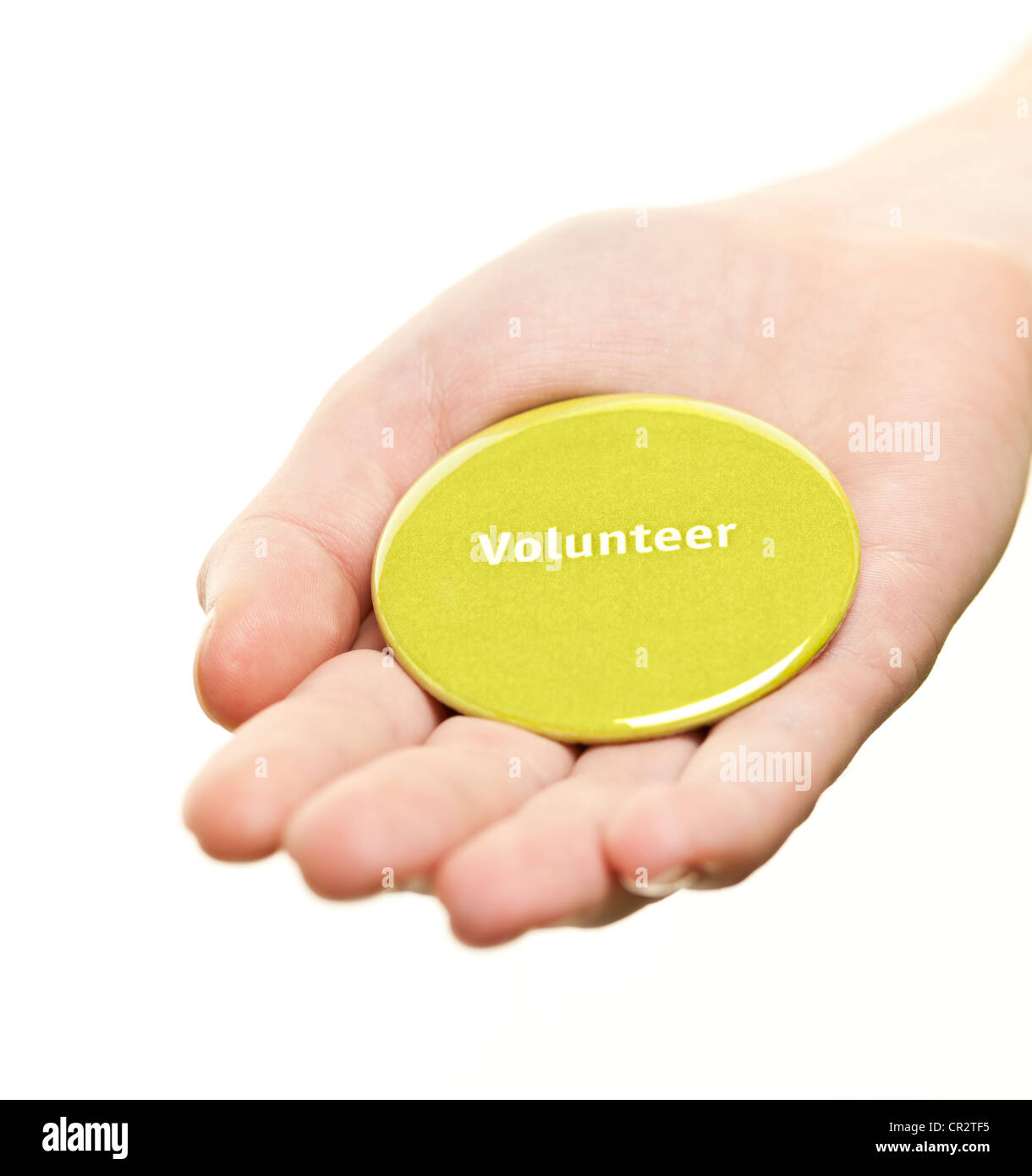 Hand holding green round volunteer button isolated on white - Stock Image