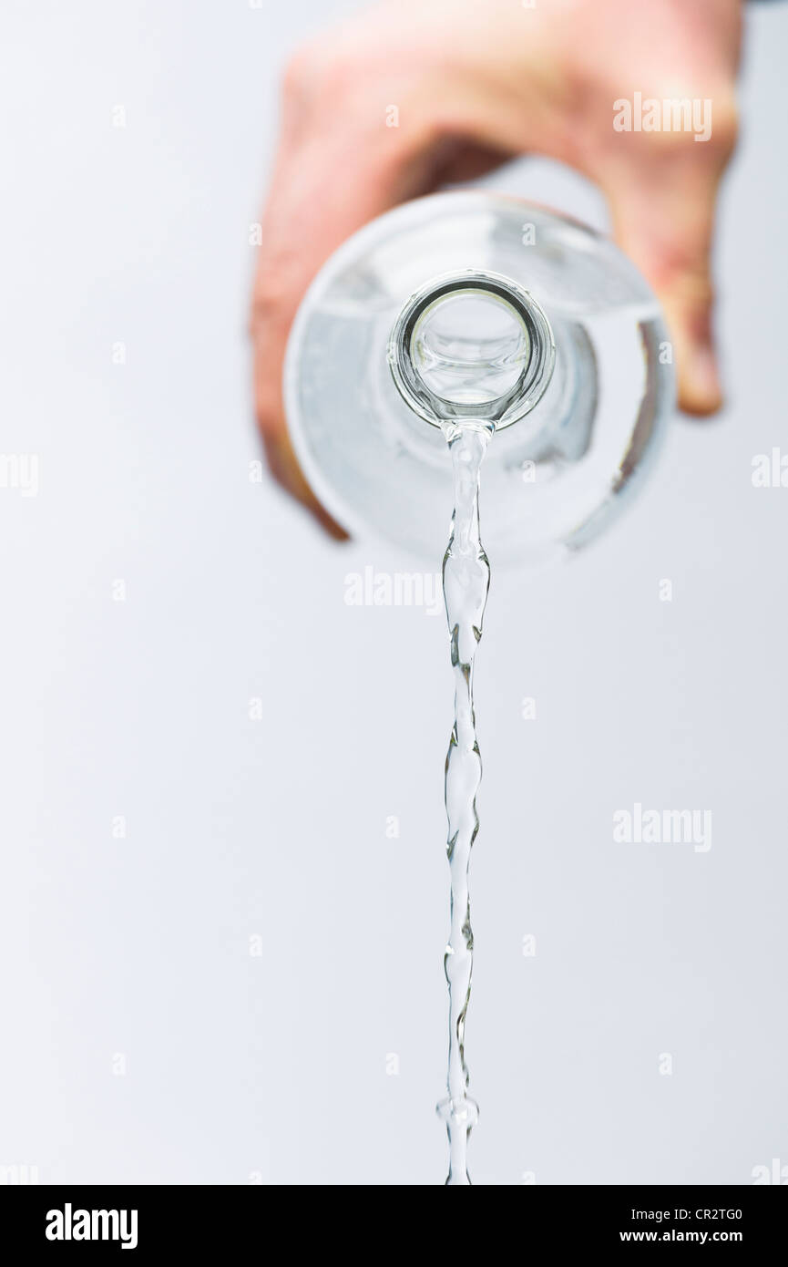 Hand pouring mineral water from a glass bottle against white background Stock Photo