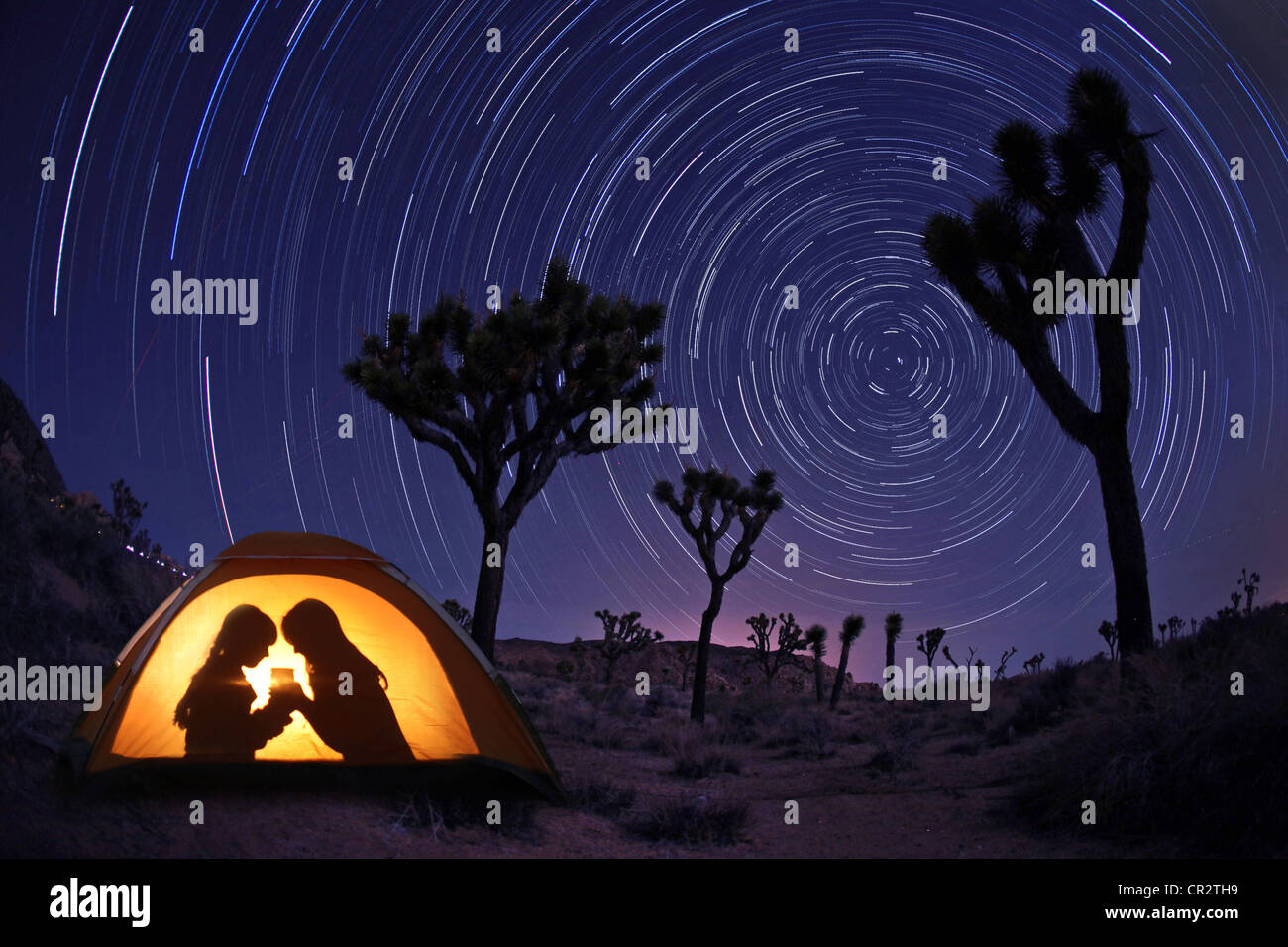 Children Camping at Night in a Tent With Star Trails - Stock Image