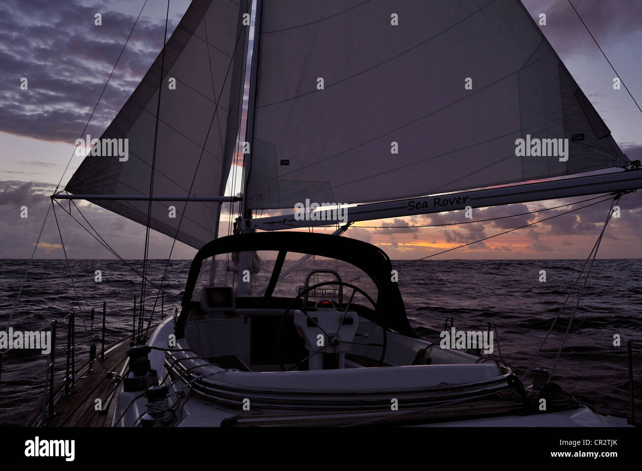 A cruising yacht  sailing with poled out genoa and mainsail in early morning light, offshore in the South Pacific - Stock Image