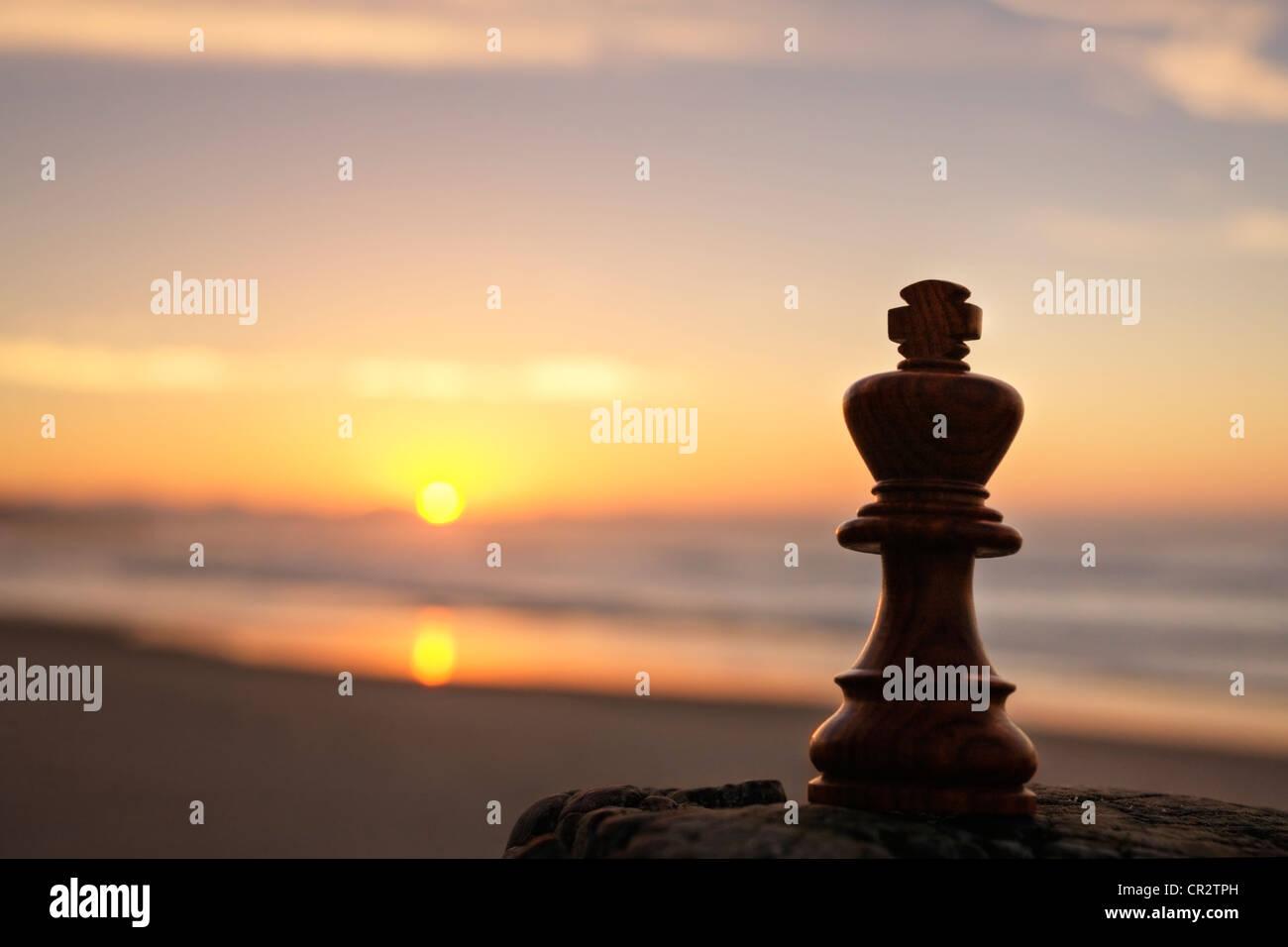 chess king on beach at sunrise - Stock Image