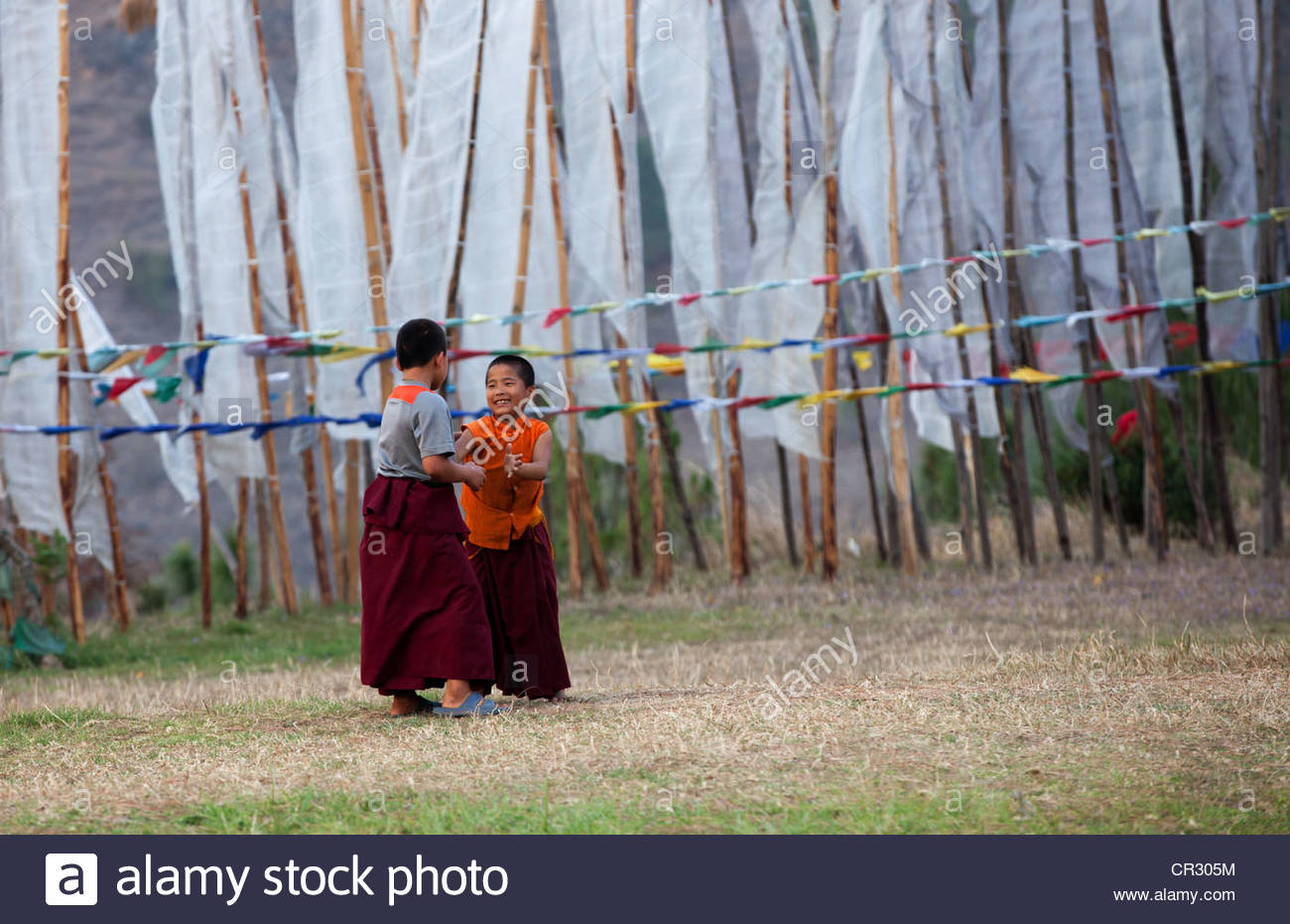 Young monks at play at Chimi Lhakhang or fertility temple in Lobesa Village, Punakha, Bhutan. - Stock Image