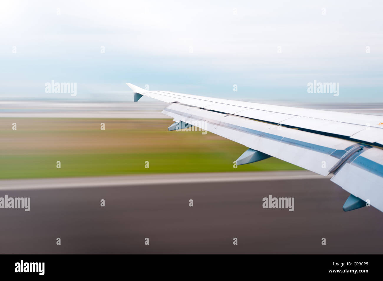 View of air plane wing during take off or landing. Motion blur of airport grounds and sky. Stock Photo