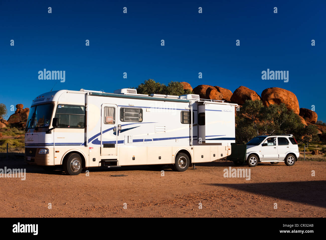 Campervan with a car attached to the back, parked on a campsite, Devils Marbles, Northern Territory, Australia - Stock Image