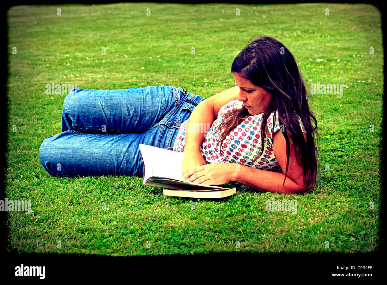 Instagram sytle image of an adult female enjoys reading on a summers day on the grass in the park - Stock Image