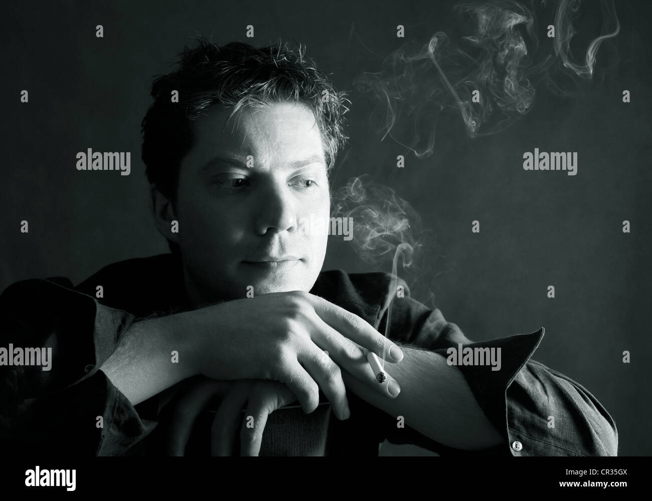 The thoughtful man with a cigarette in studio - Stock Image