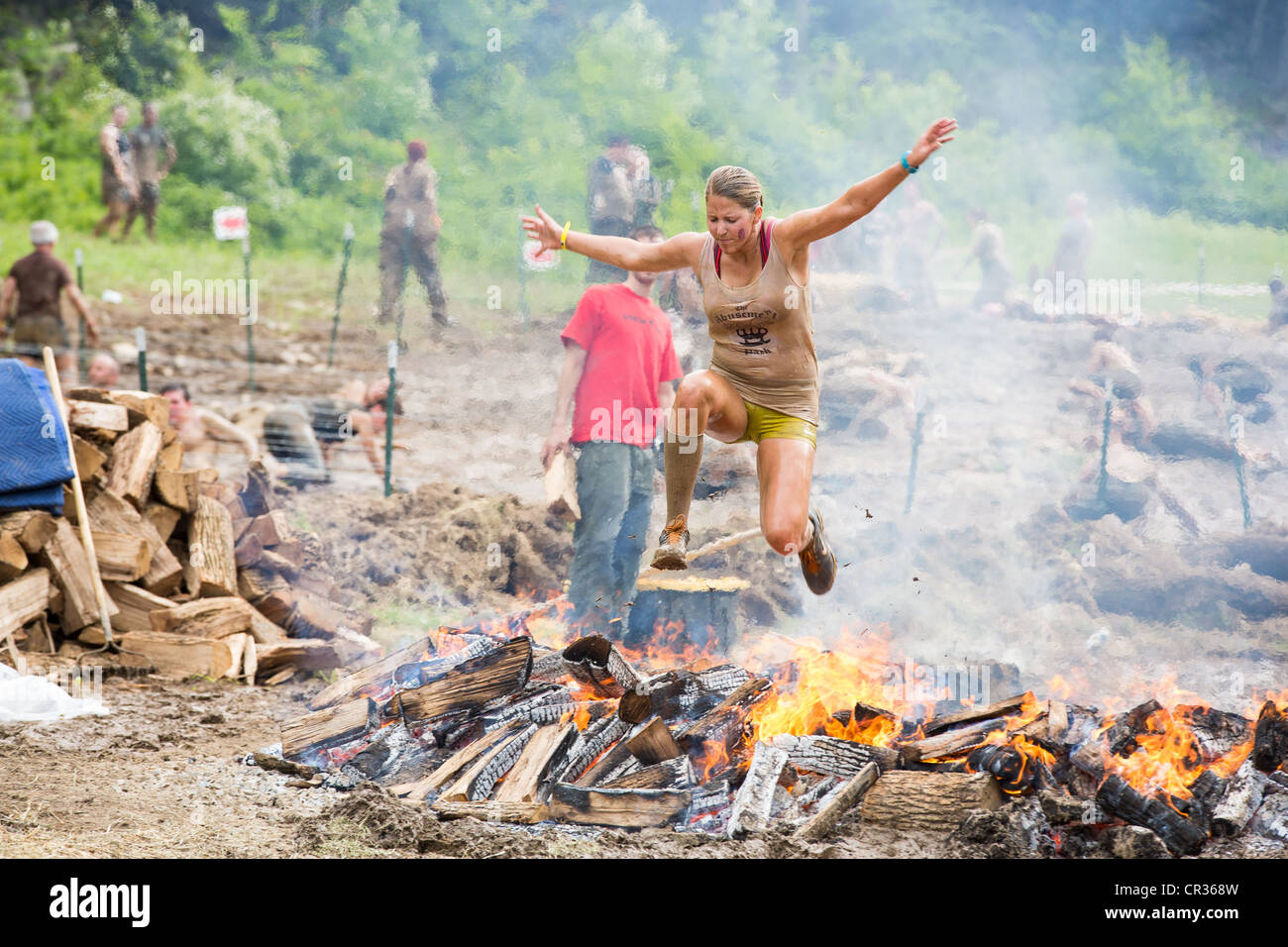 Participants of challenging sprint obstacle trail race, Spartan Race in Tuxedo New York, running in mud, jumping - Stock Image
