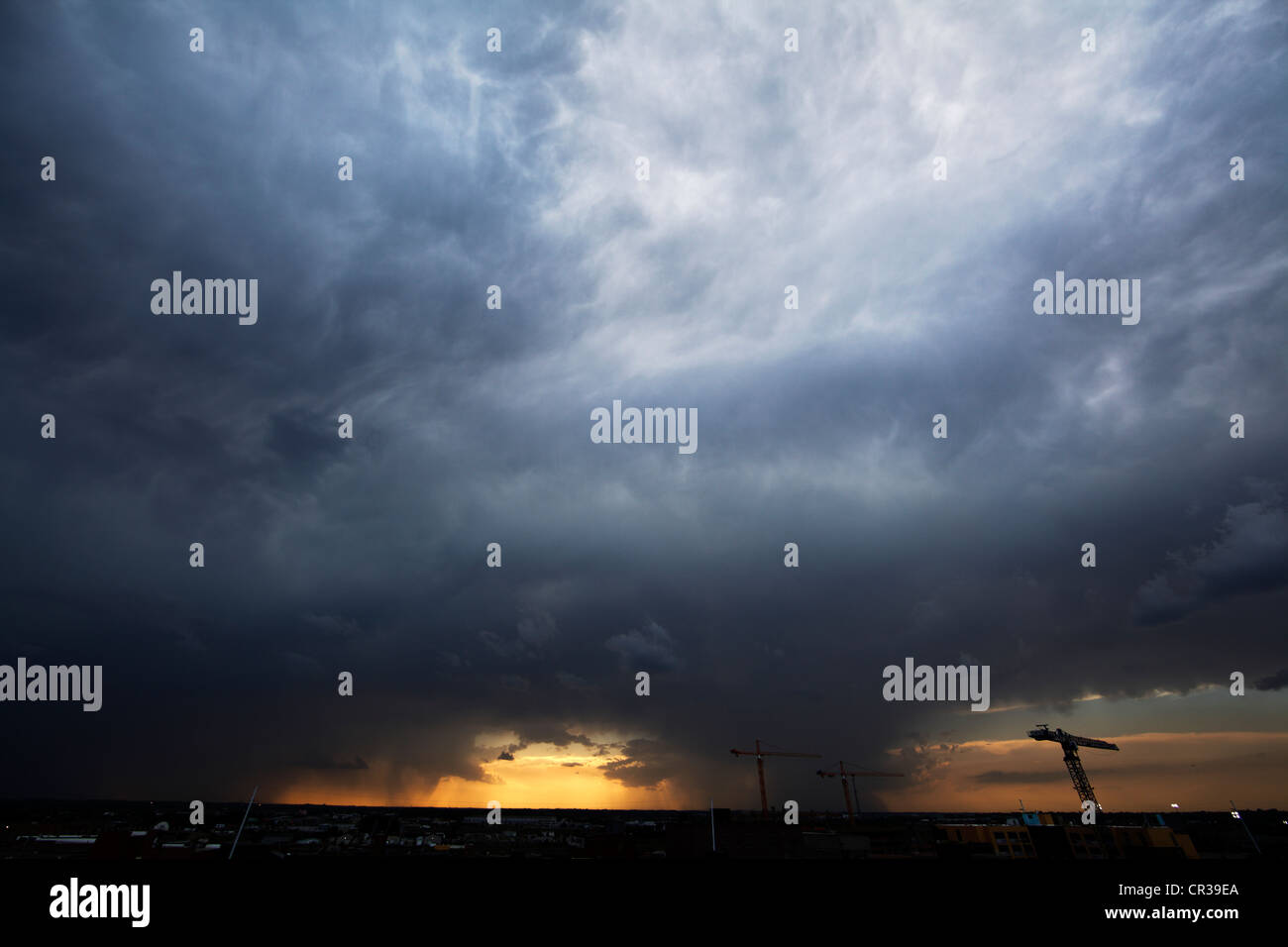 Two areas of very heavy rainfall in a thunderstorm, showing tower cranes and mammatus clouds. - Stock Image