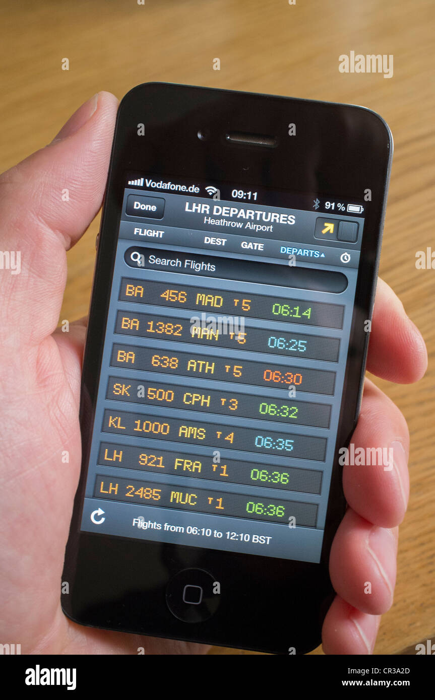 Man using flight tracking App to look at live flight departures board at Heathrow Airport on an iPhone 4G - Stock Image