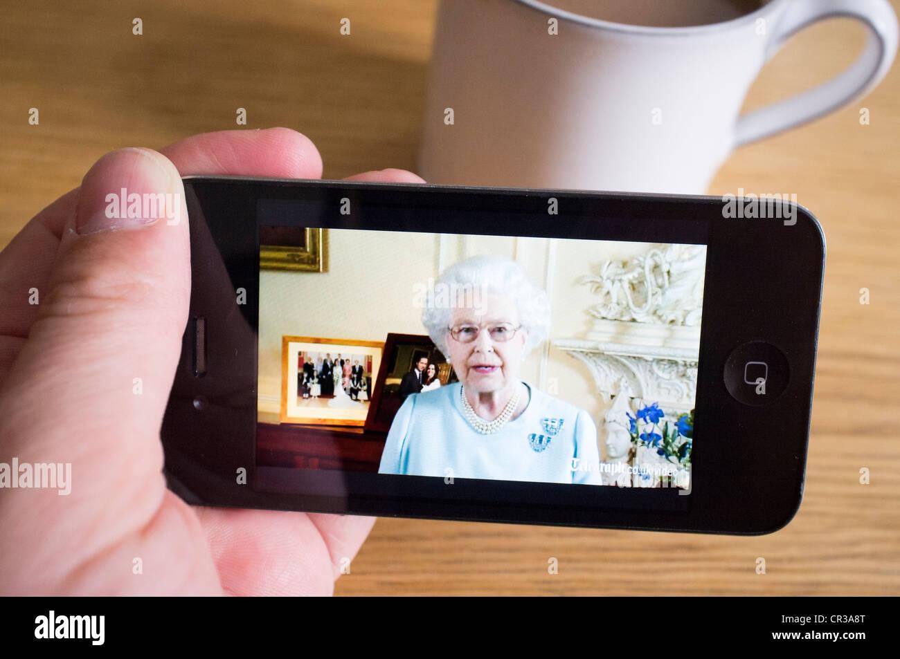 watching Queen's Diamond Jubilee speech on streaming video news website on an iPhone smartphone - Stock Image