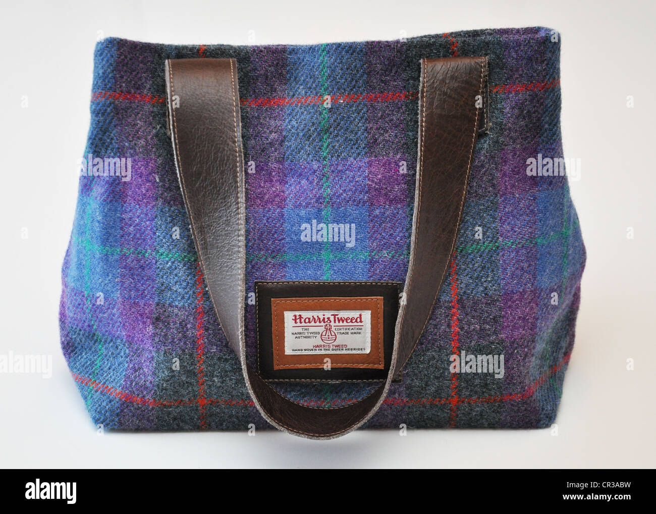 2fa6b2bcaf61 Blue and purple Harris Tweed bag with leather handle against a white  background - Stock Image