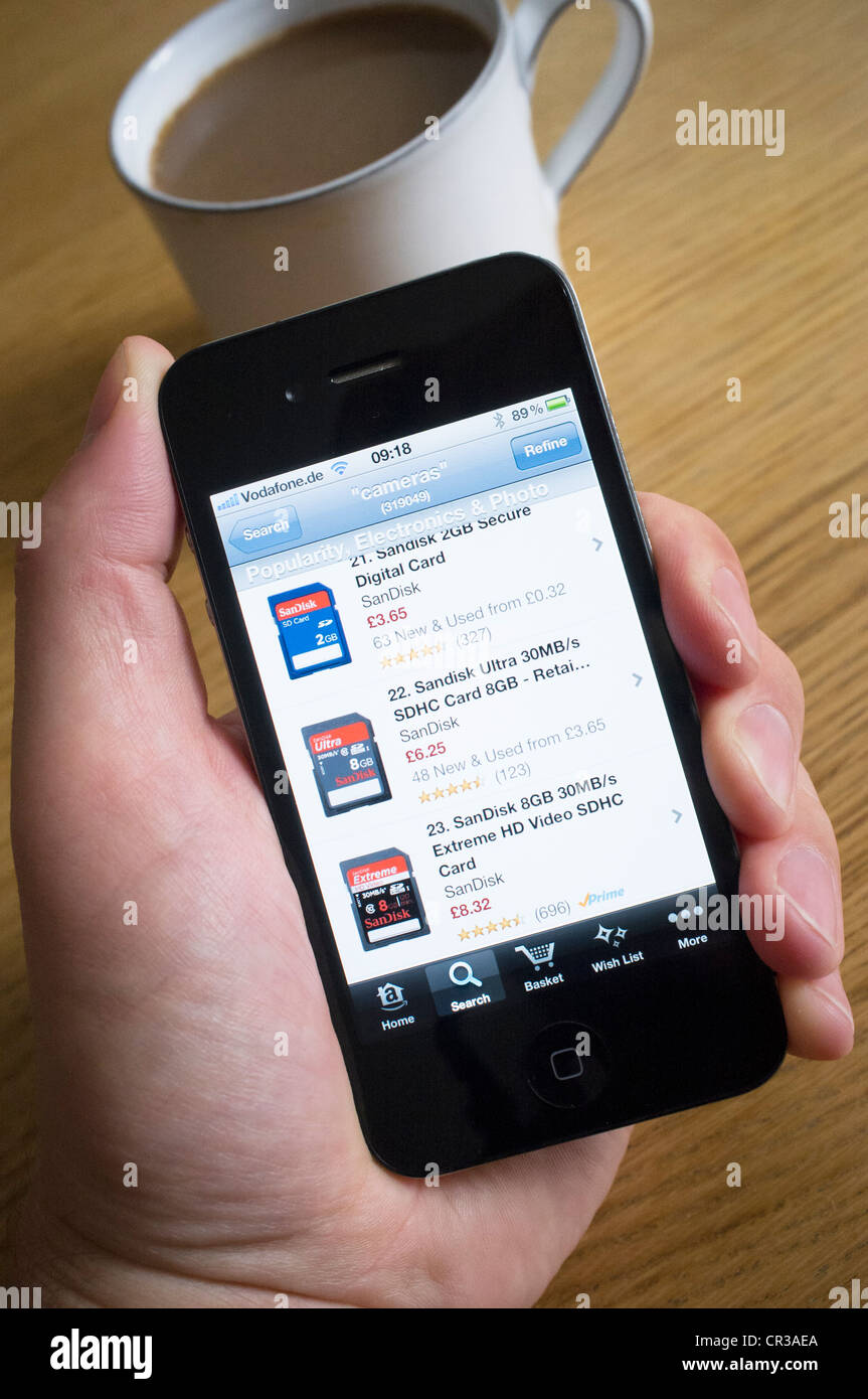 Using an iPhone 4G smart phone to buy electronics products from Amazon.com online shop - Stock Image