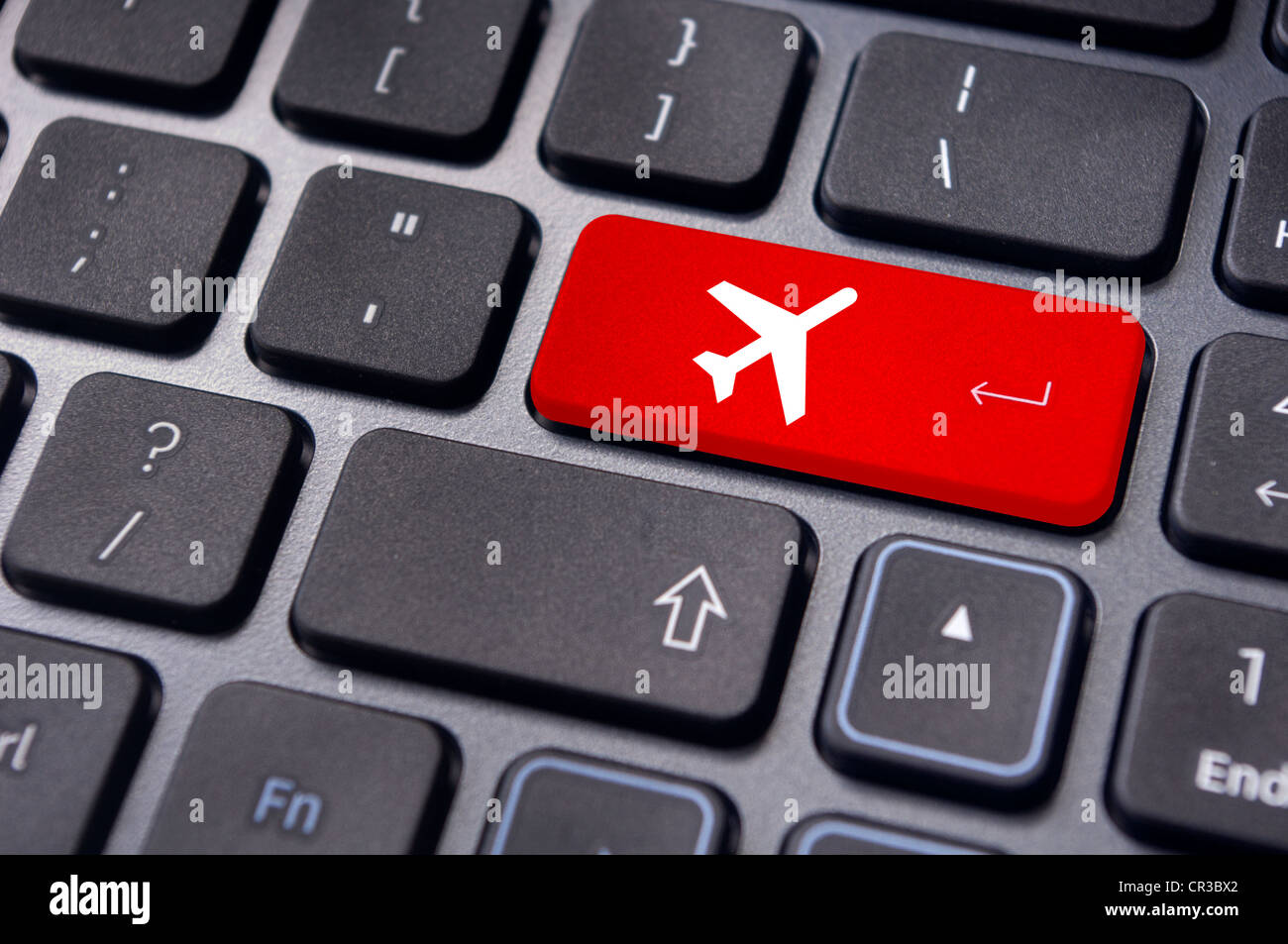 a plane sign on keyboard, to illustrate online booking or purchase of plane ticket or business travel concepts. - Stock Image