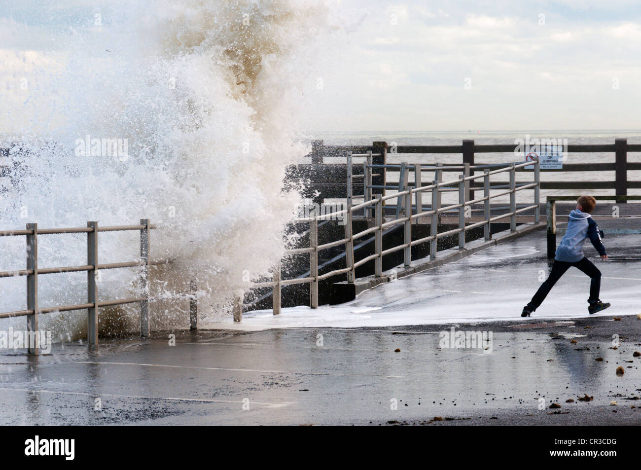 A young boy dodging the waves breaking over the harbour wall at Broadstairs in Kent. - Stock Image