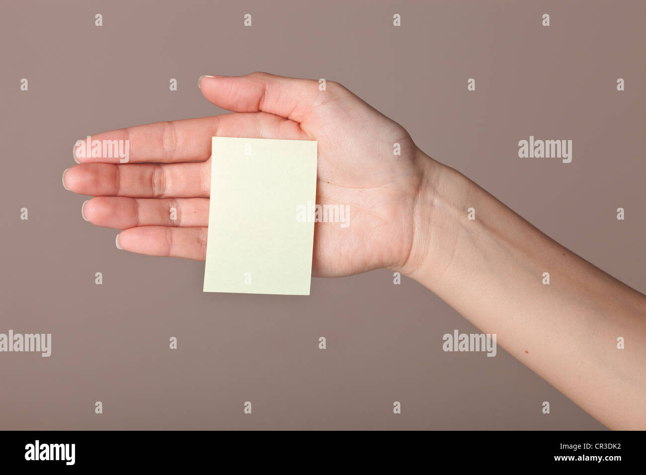 Post-It note stuck to the palm of a female hand - Stock Image