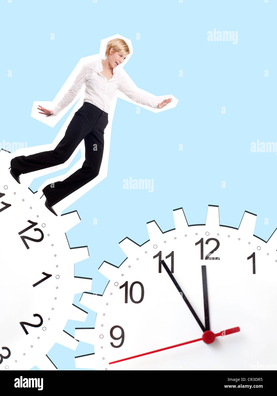 Young business woman between two clocks, composing - Stock Image