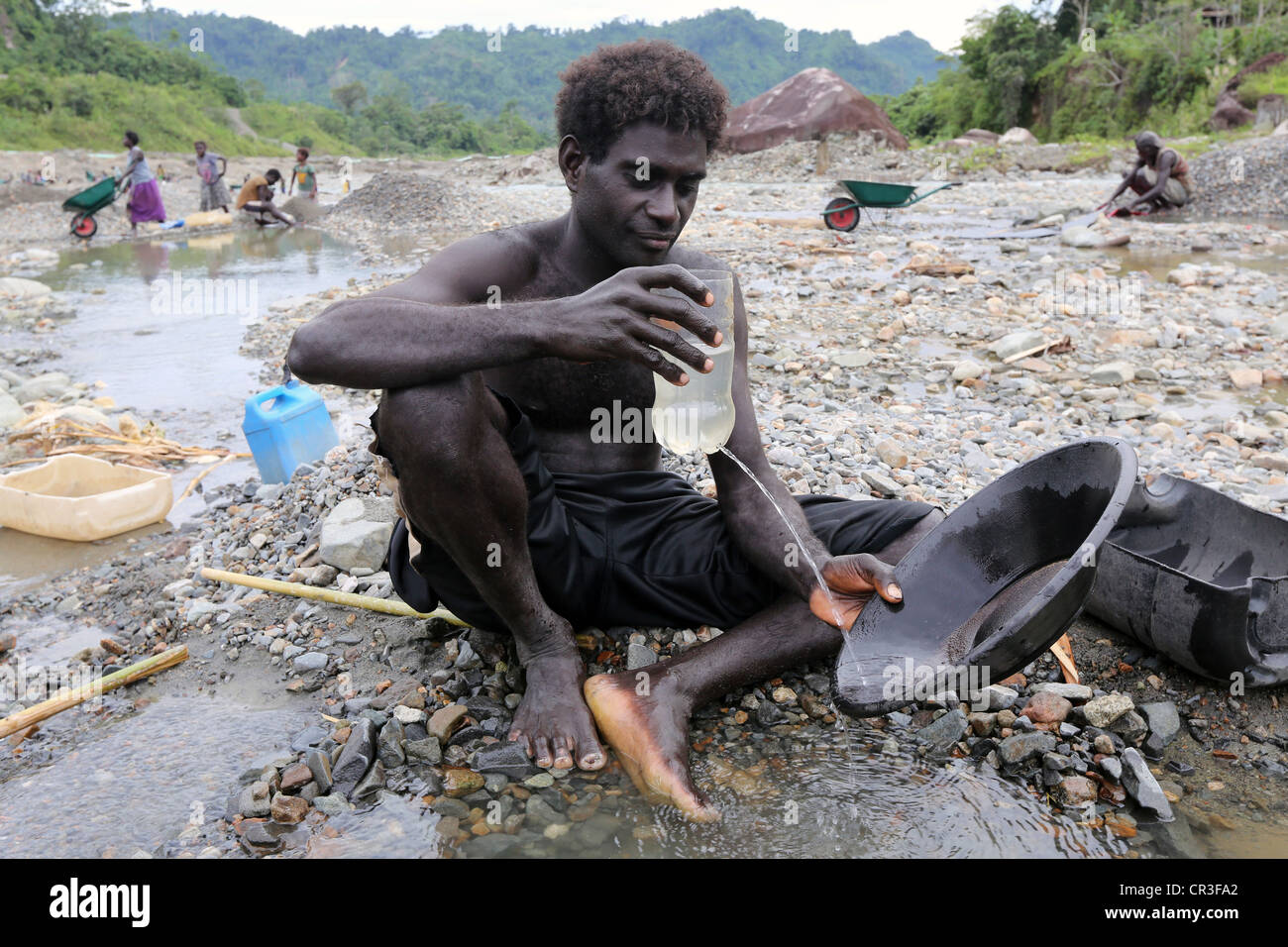 Man panning gold in the polluted Jaba river flowing from Panguna copper mine. Autonomous Region of Bougainville, - Stock Image