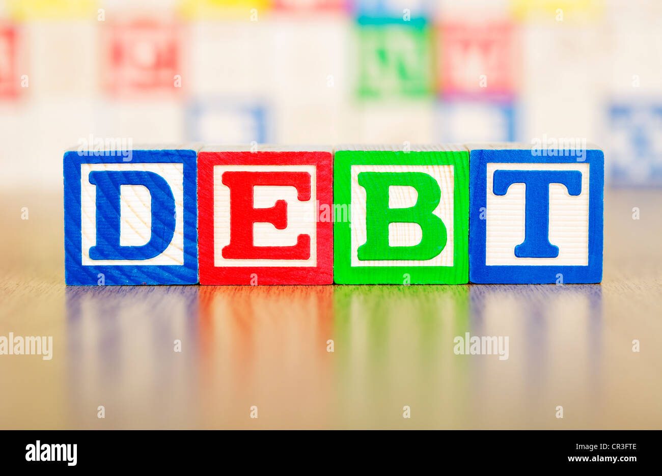 Debt Spelled Out in Alphabet Building Blocks - Stock Image