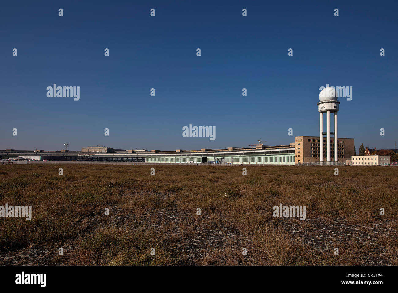 View from the former airfield of to the Tempelhof airport building with airplane hangards, park on Tempelhofer Feld - Stock Image