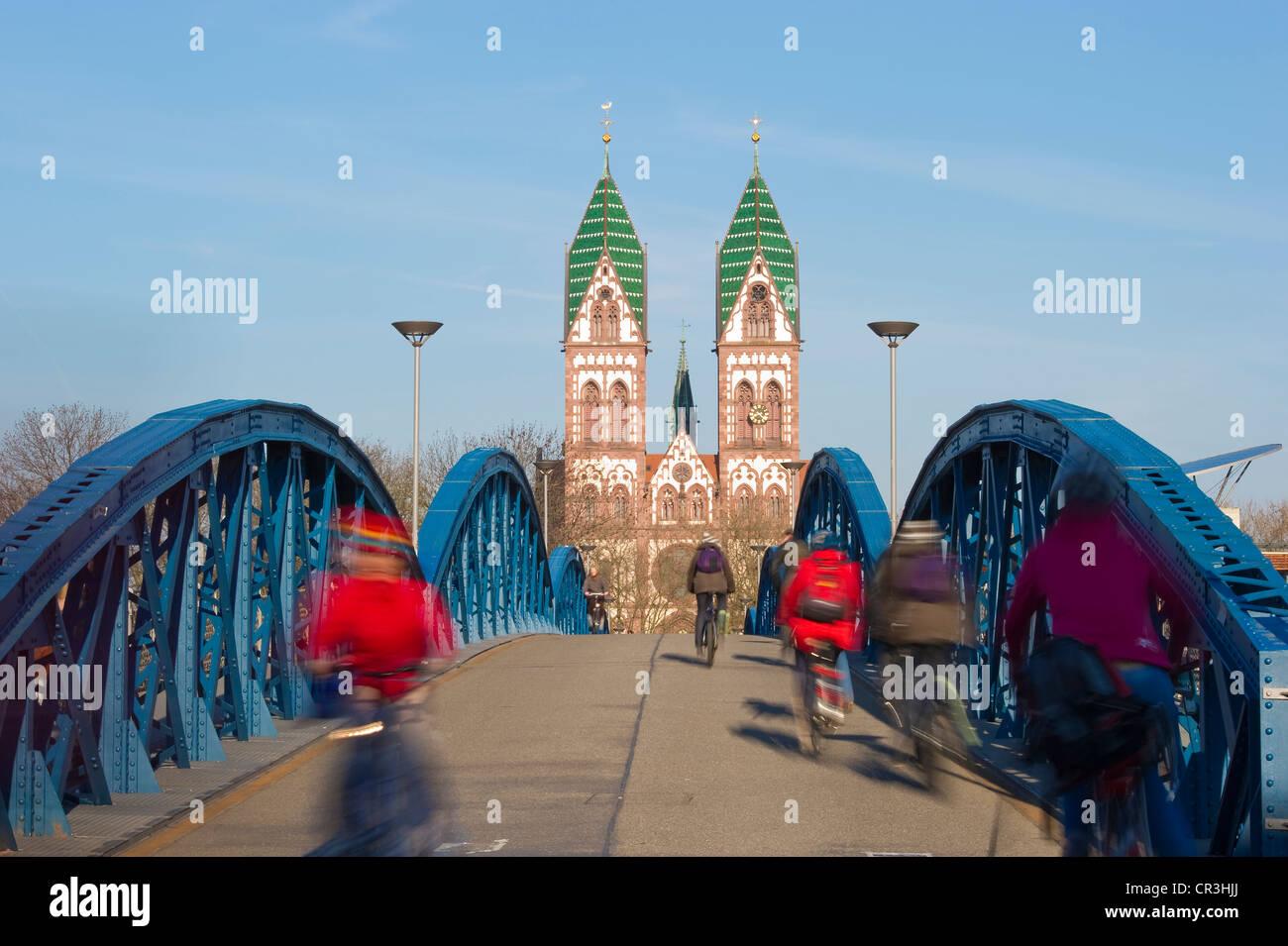 Blue Bridge and cyclists with motion blur, Freiburg im Breisgau, Black Forest, Baden-Wuerttemberg, Germany, Europe - Stock Image