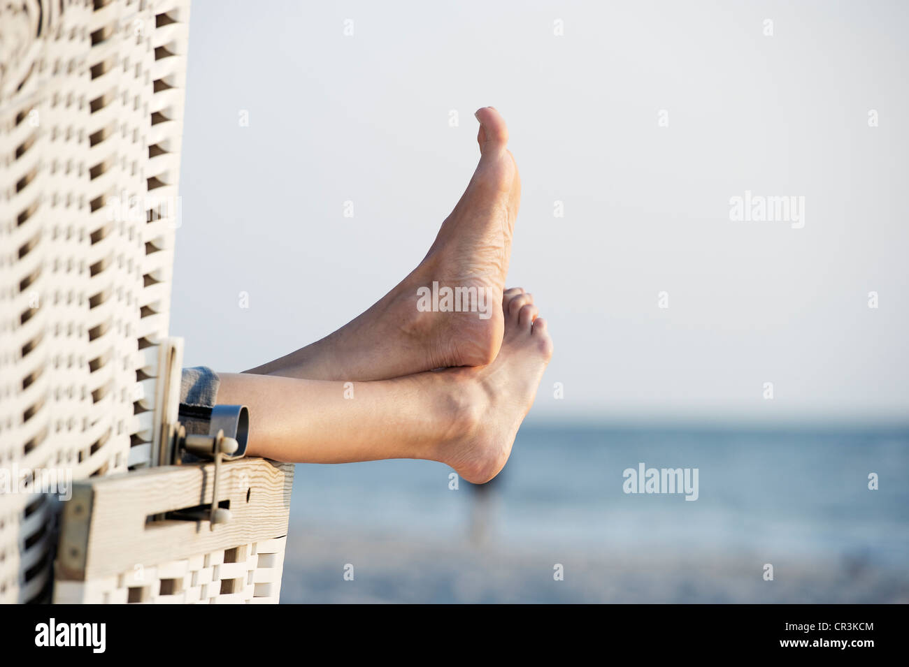 Roofed wicker beach chair and bare feet, Westerland, Sylt island, Schleswig-Holstein, Germany, Europe - Stock Image