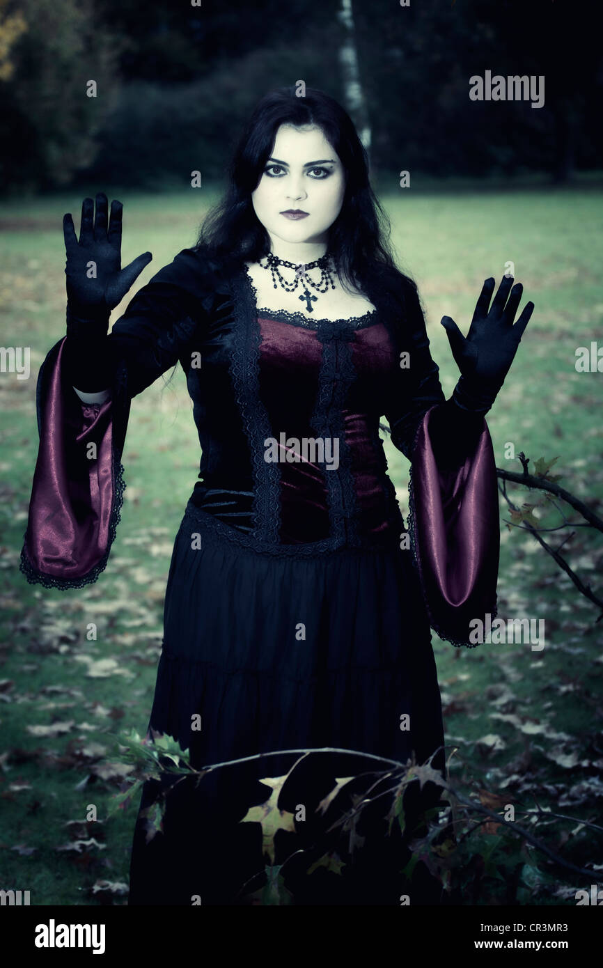 Woman, Gothic, standing, serious, raised hands - Stock Image