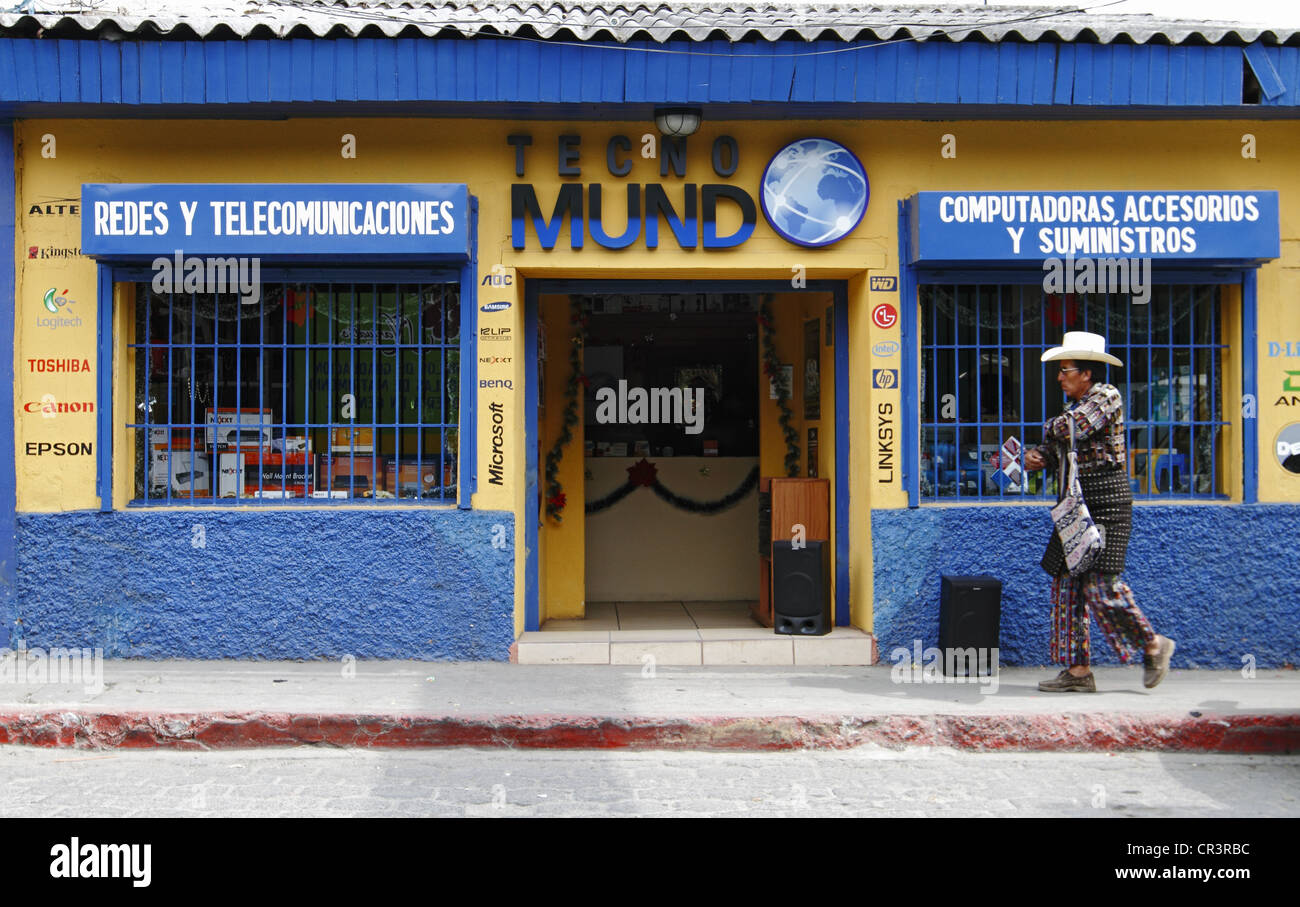A man with traditional dress passes by a telecommunication shop, Solola Department, Guatemala, Central America - Stock Image