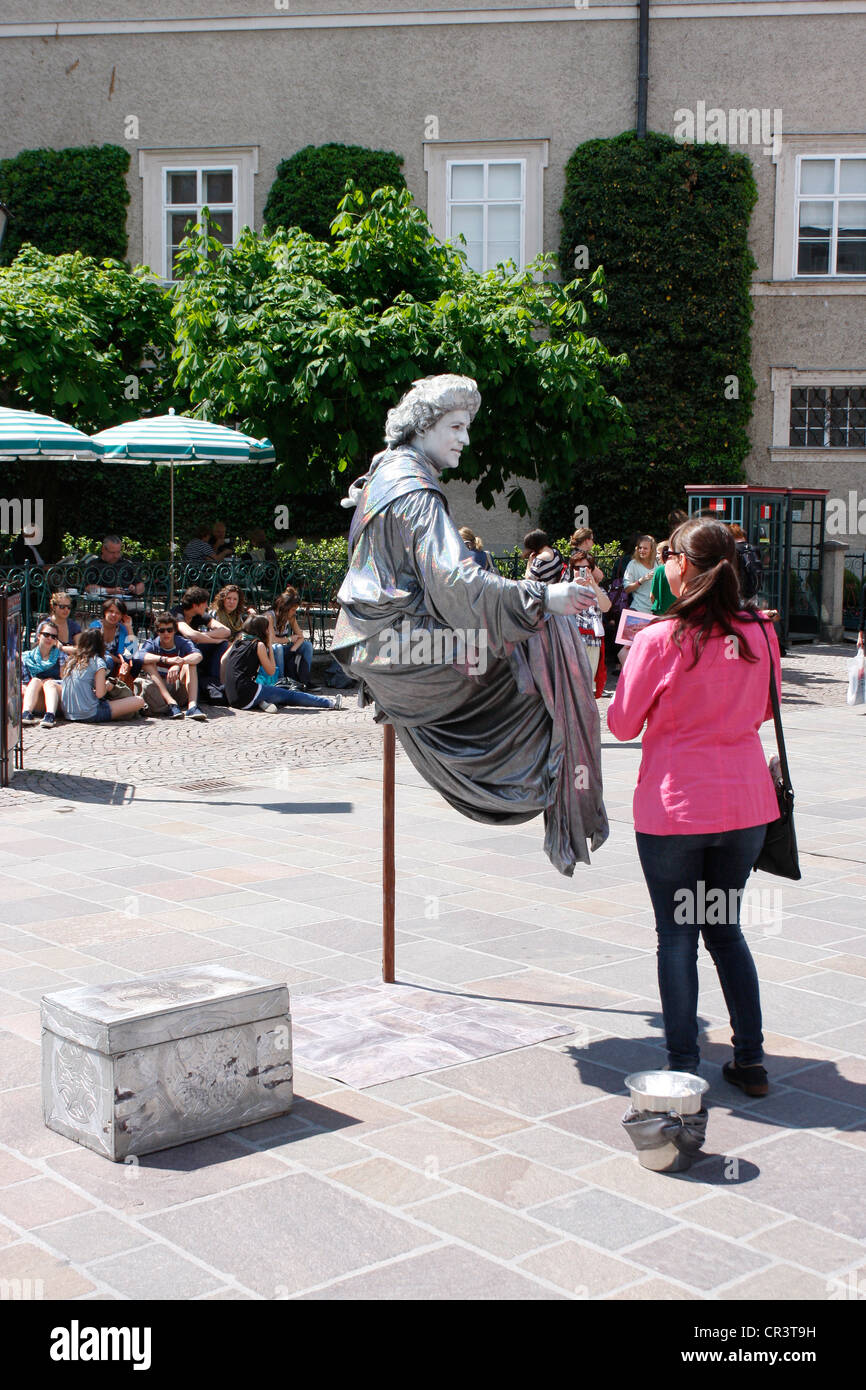 Street mime artist  clever performance in Salzburg city Old Town,Austria. - Stock Image