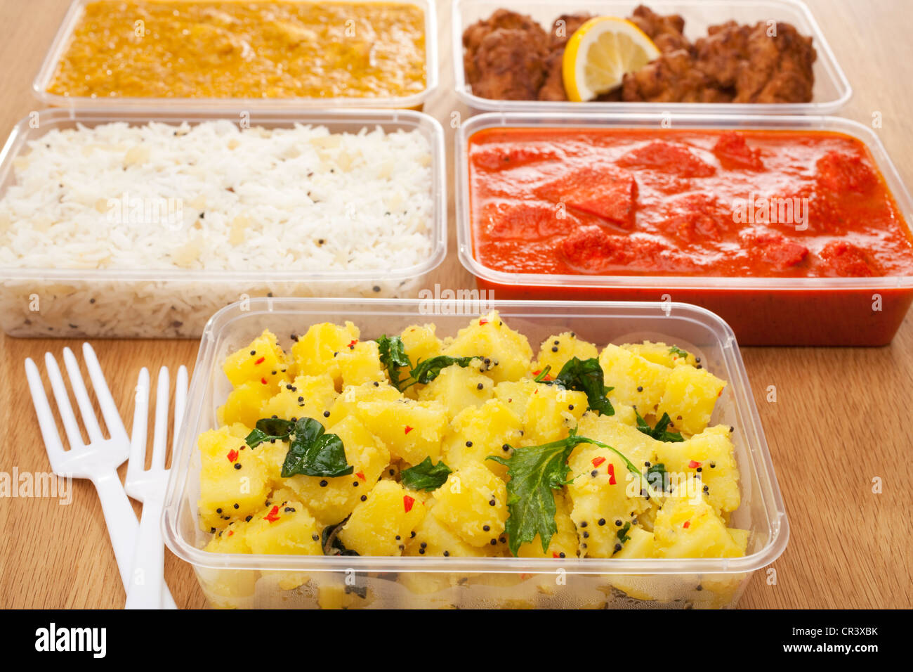A selection of Indian takeaway food in plastic containers - Stock Image