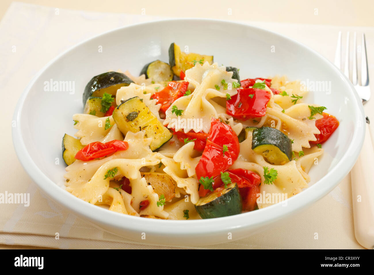 A bowl of pasta bows or farfalle with roast courgettes or zucchini, red pepper and tomato with olive oil and herbs. Stock Photo