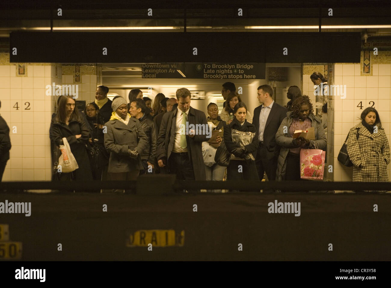 Commuters wait on the platform for a downtown subway train at Grand Central Station in NYC Stock Photo