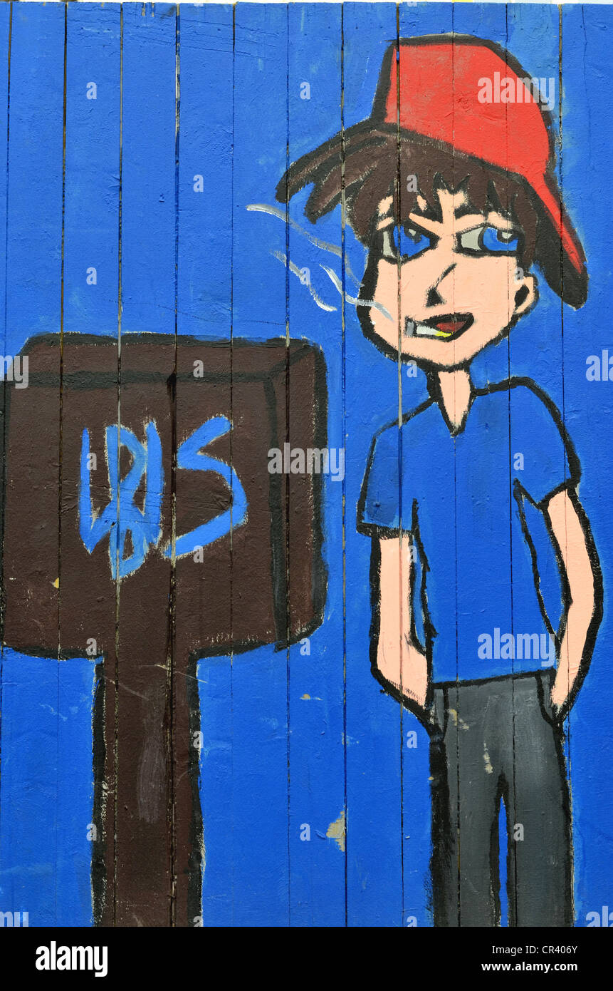 Naughty teenager wearing baseball cap smoking a cigarette, painted fence, designed by pupils, Muelheim an der Ruhr, Stock Photo