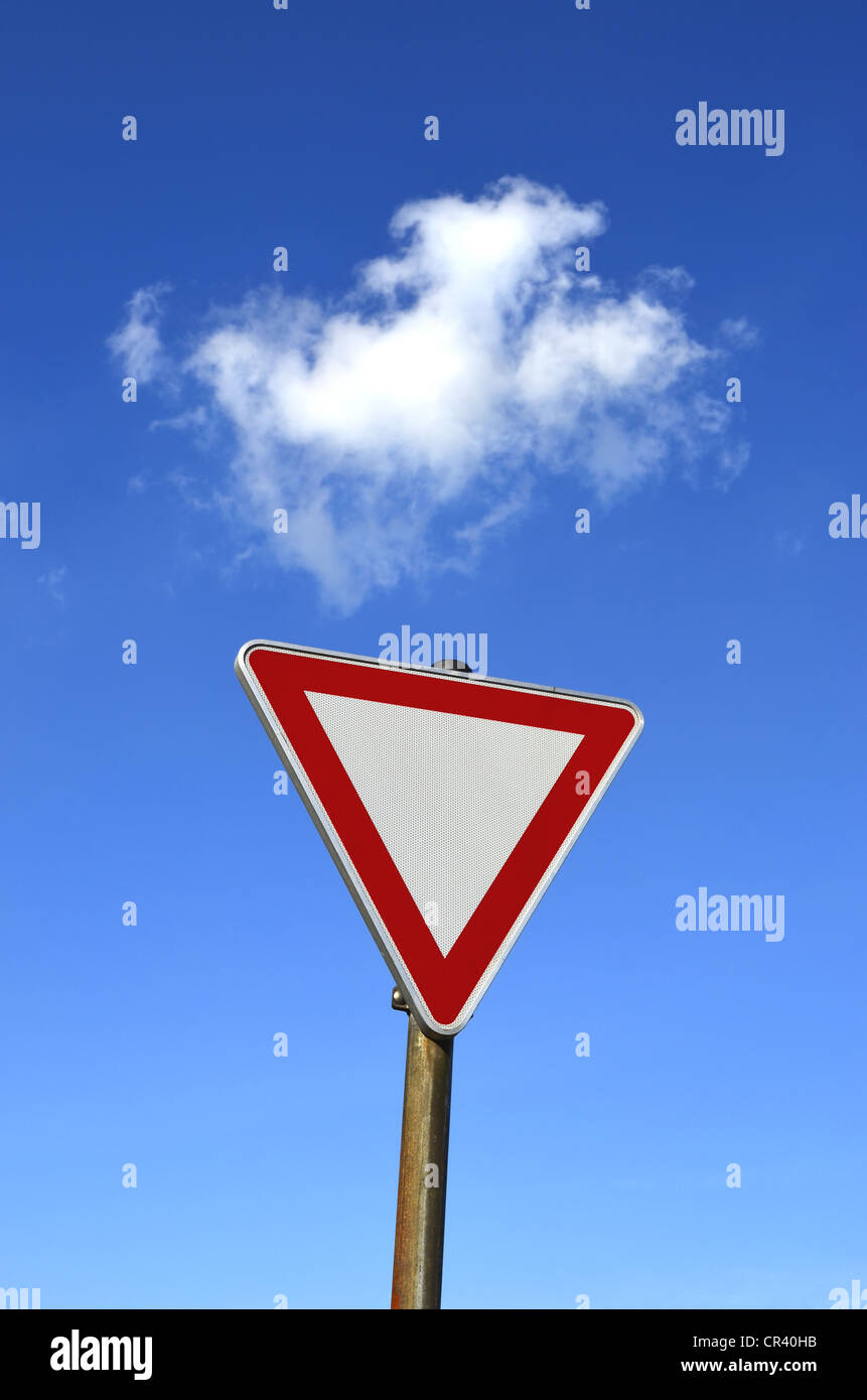 Traffic sign, give way, against a blue sky with clouds, Germany, Europe - Stock Image