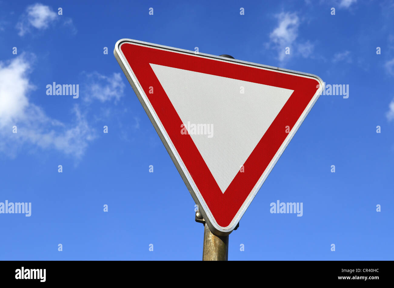 Traffic sign, give way, against a blue sky with clouds - Stock Image