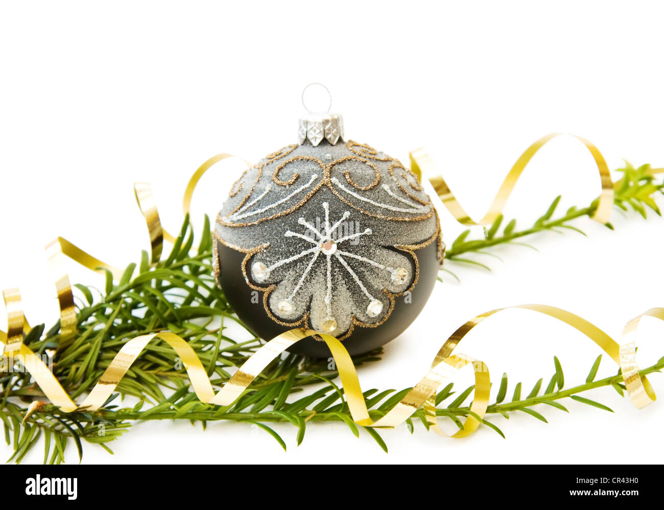Celebrating Christmas with traditional pine tree branch and silver bauble decoration. Isolated on white. - Stock Image