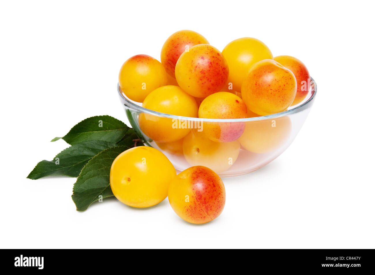 glass bowl of the yellow damson plum isolated on a white background - Stock Image