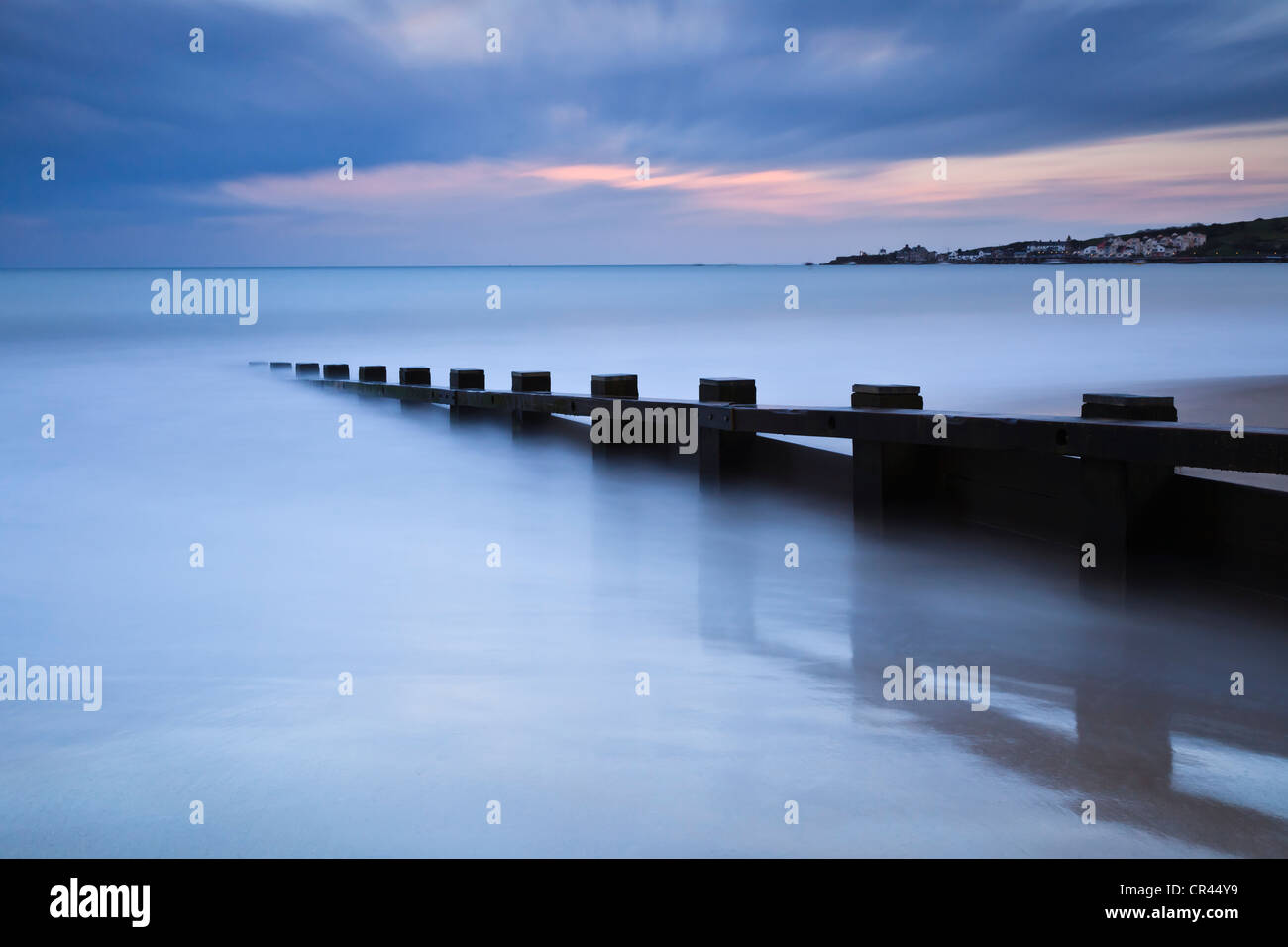 Dusk, Swanage Bay, Dorset, UK looking towards the town from the north beach, with a wooden groyne in the foreground. - Stock Image