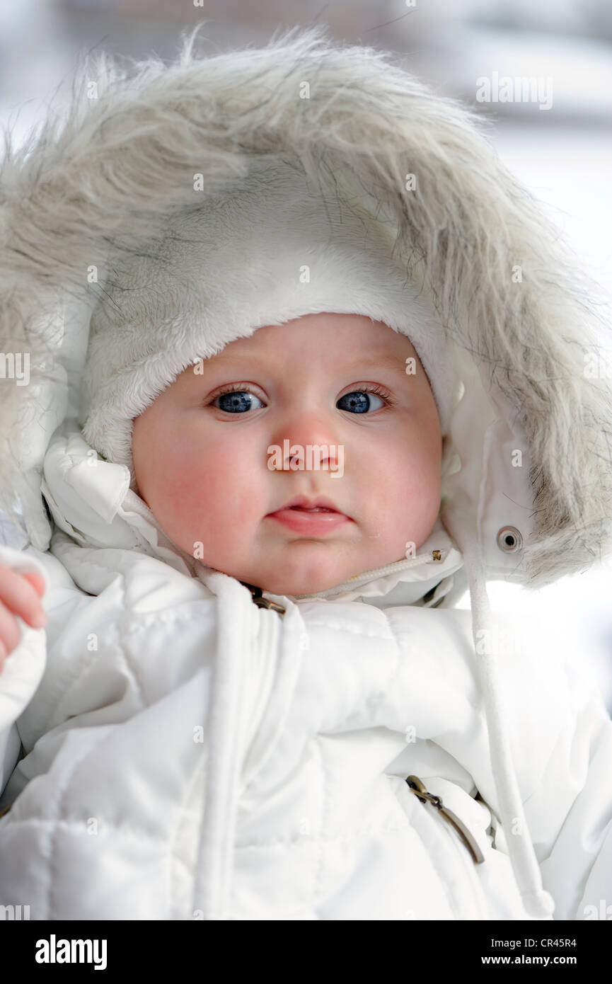 Baby, 6 month, wrapped in very warm winter clothing - Stock Image