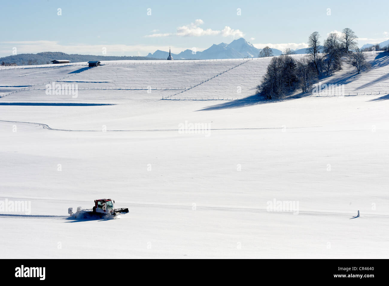 Cross country ski-run track-setter and the tower of the parish church Maria Heimsuchung, Visitation of Mary, Grosshartpenning, - Stock Image