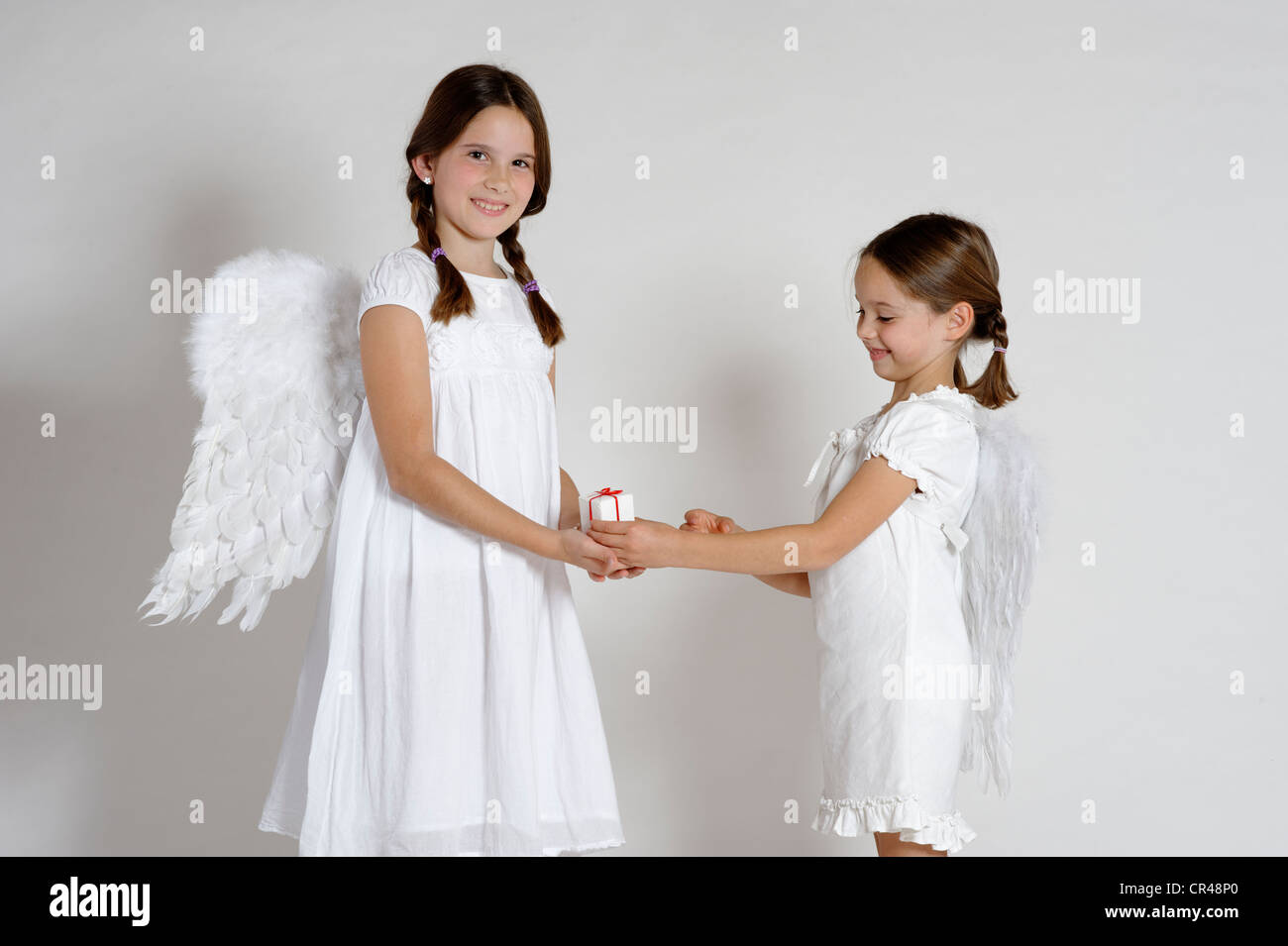 Two girls dressed up as Christmas angels, with a gift, Christmas - Stock Image