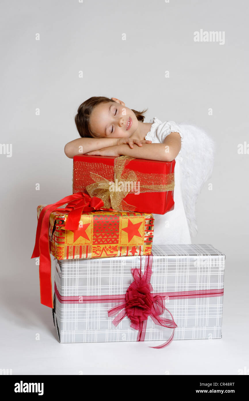 Girl dressed up as a Christmas angel with gifts, Christmas - Stock Image