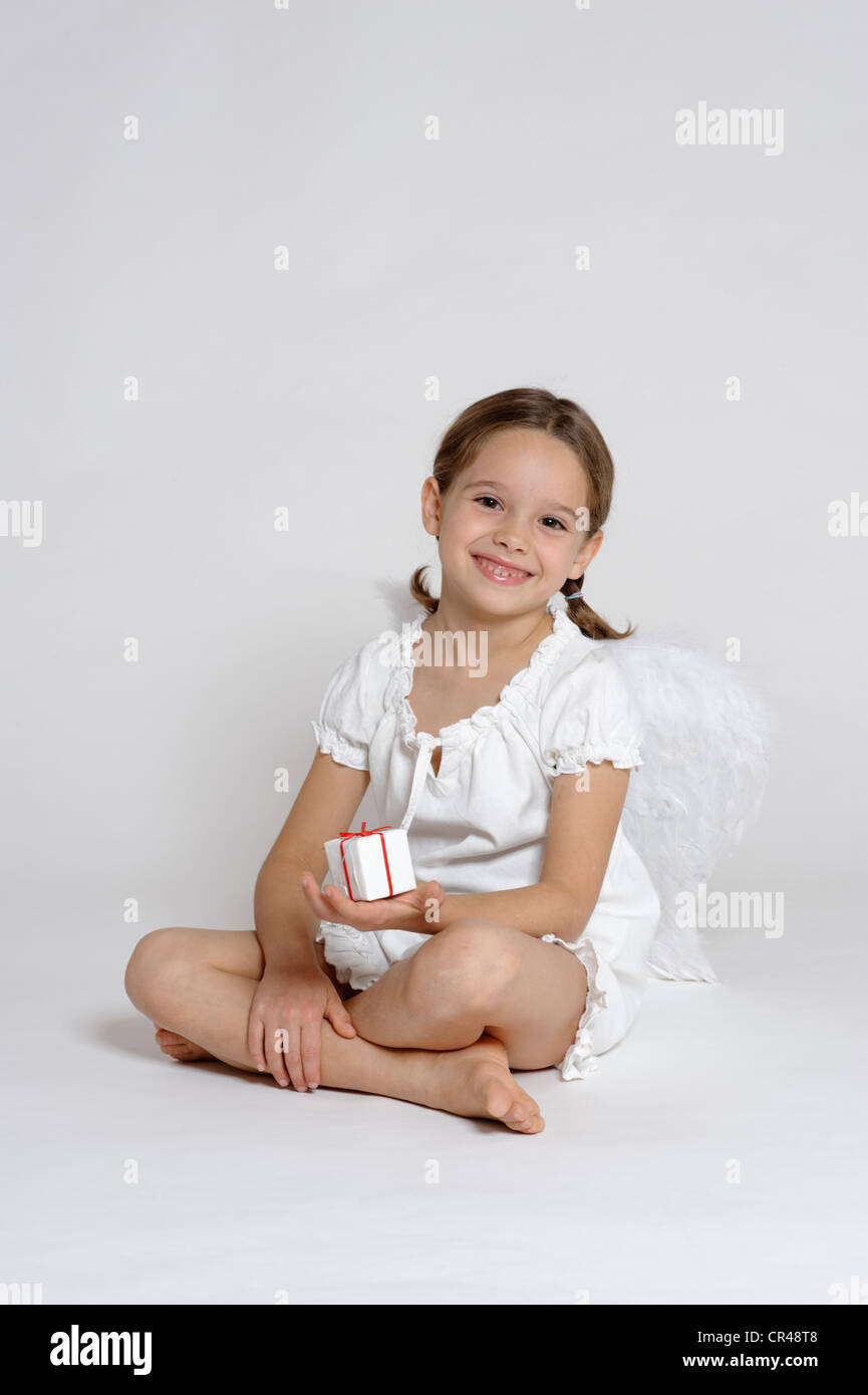 Girl dressed up as a Christmas angel with a gift, Christmas - Stock Image