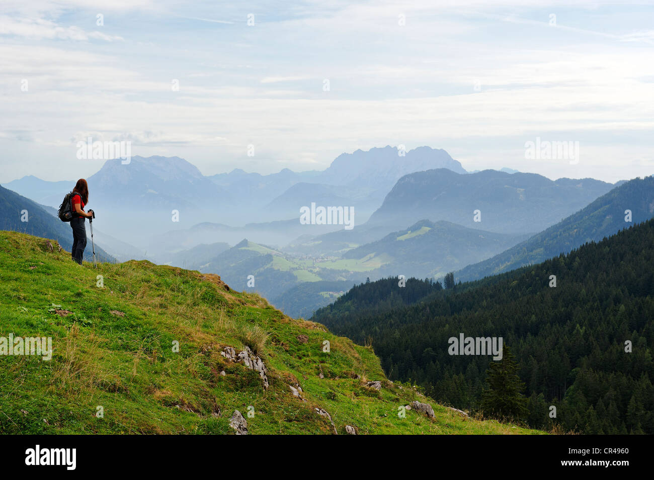 Hiker standing on the Ackernalm alp, view of the Inn Valley and the Kaisergebirge mountains, Tyrol, Austria, Europe - Stock Image