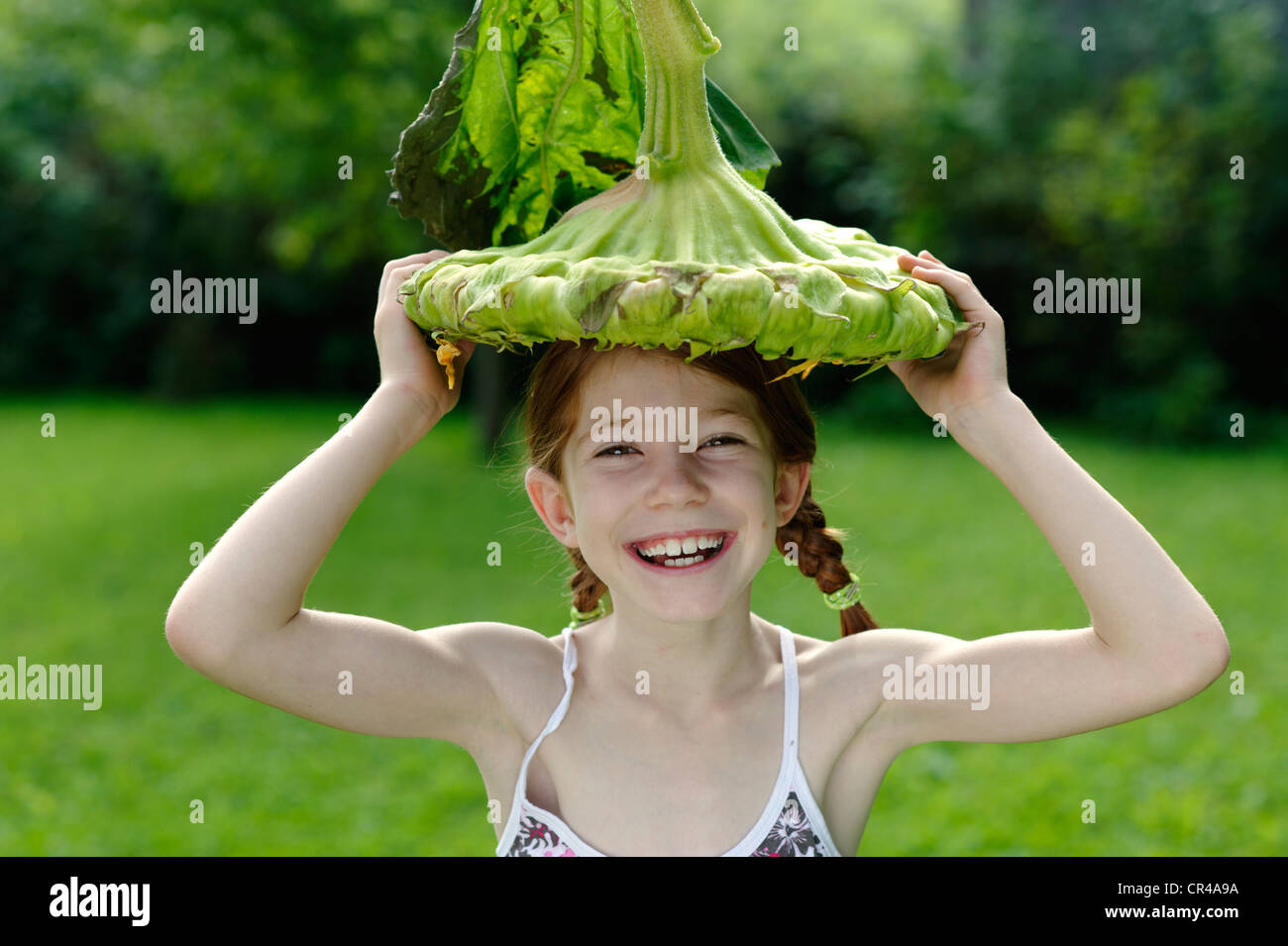 Girl with a big sunflower as a hat - Stock Image